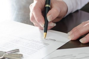 Woman signing a real estate contract on a desk